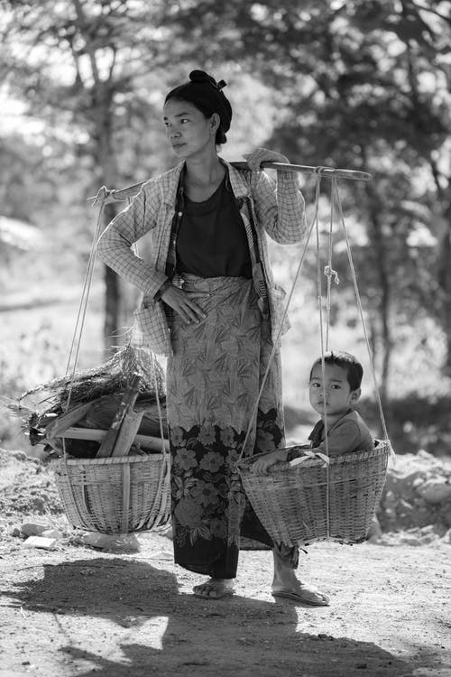Woman Carrying Baskets With Child and Woods
