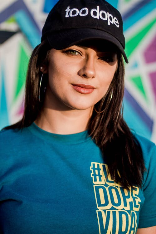 Woman in Blue Crew Neck Shirt Wearing Black Cap