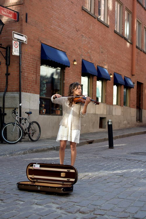 Young female street performer playing classic violin on cobblestone square in old city on sunny day