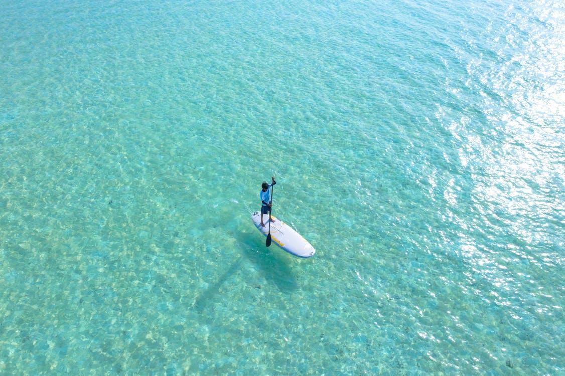 Foto De Una Persona Cabalgando Sobre Una Tabla De Surf Blanca