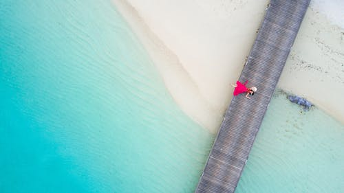 Top View Photo of Woman Lying on Boardwalk