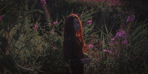 Woman Standing Near Flowering Plants