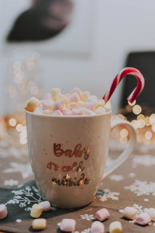 Mug with colorful marshmallows and candy cane