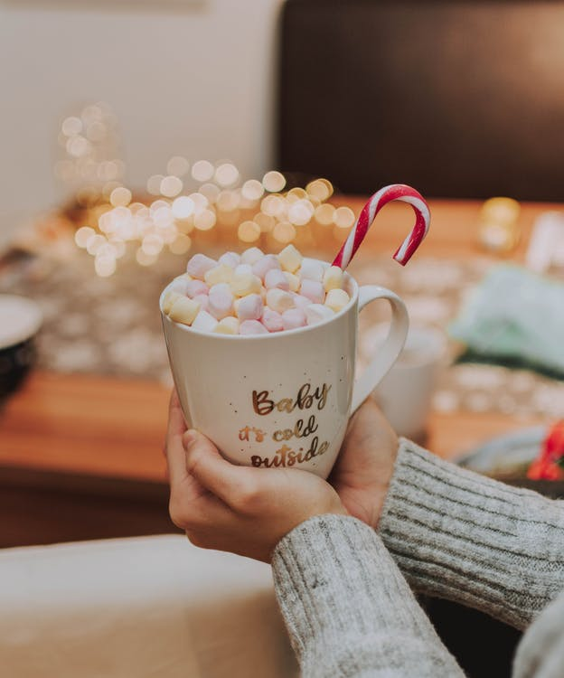 Selective Focus Photography of Person Holding Mug With Marshmallows