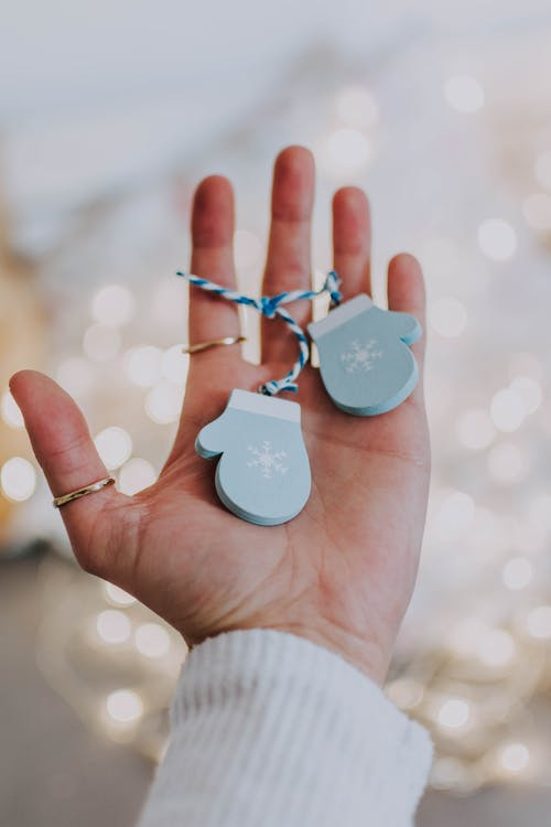 Shallow Focus Photo of Gloves Ornaments on Person's Hand