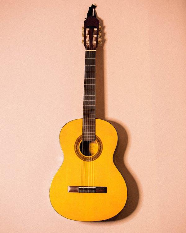 Foto De Guitarra Amarilla Colgada En La Pared Rosa