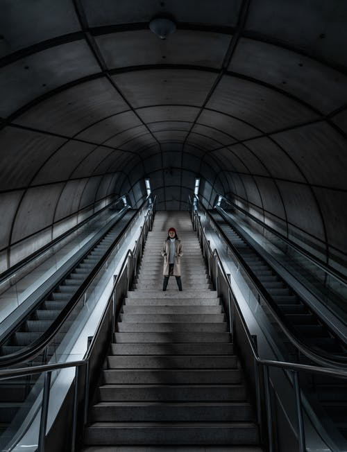 Person Standing on Stairway Beside Escalators