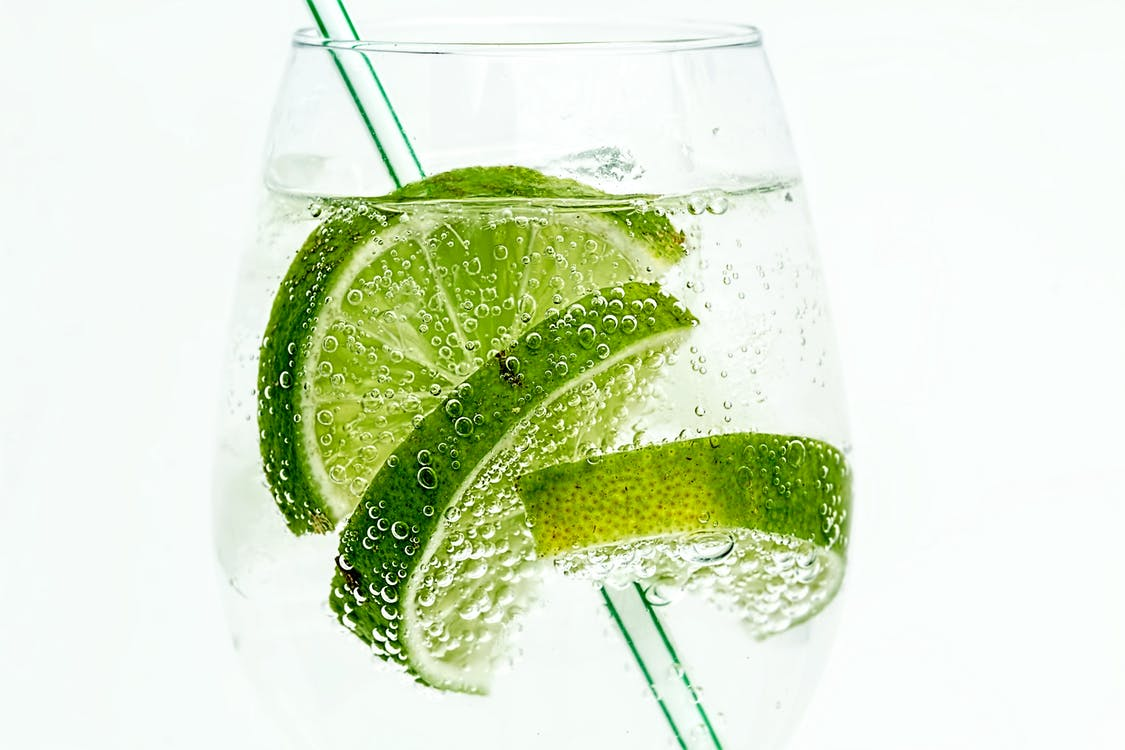 Soda With Lime on Clear Drinking Glass on White Surface