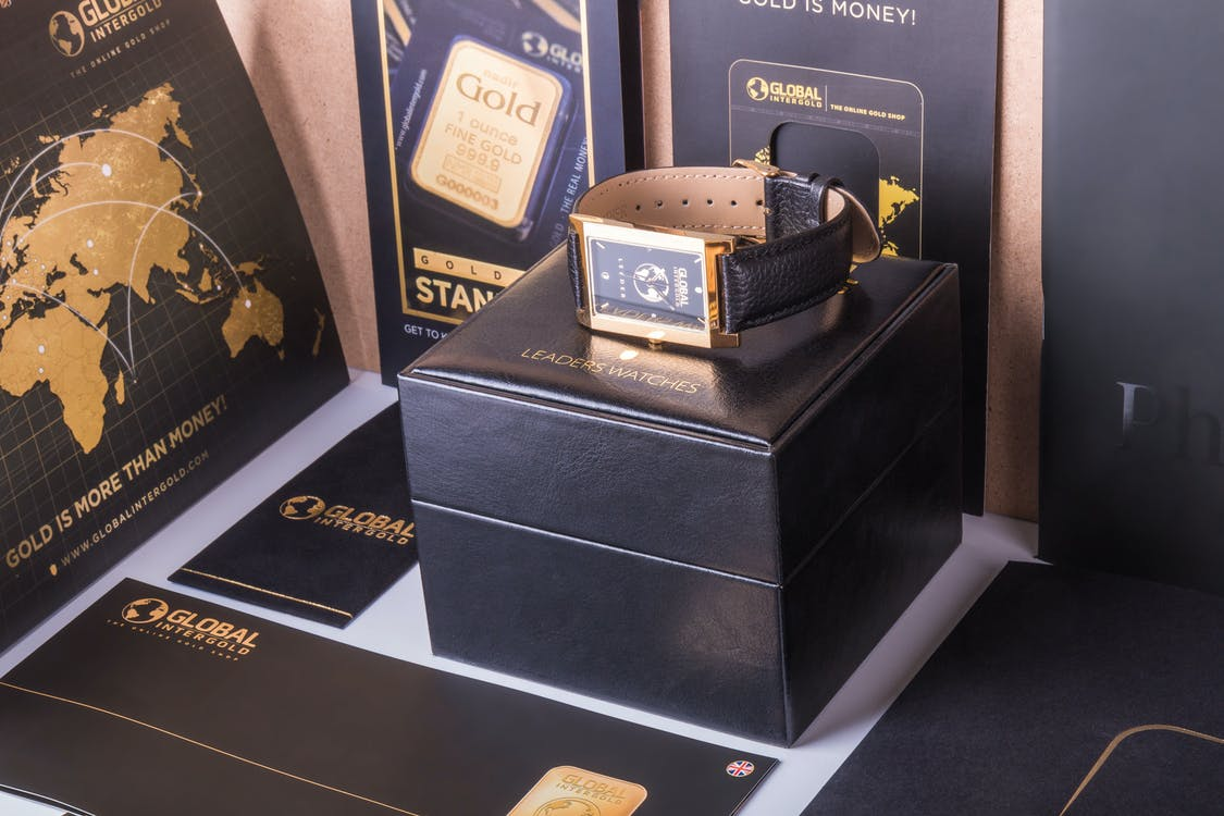 Rectangular Gold-colored Watch With Black Strap on Black Box
