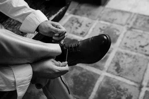 Monochrome Photo of Person Tying Shoes