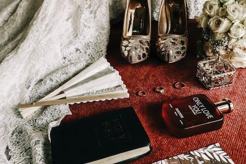 Fragrance Bottle Beside Book and Folding Hand Fan