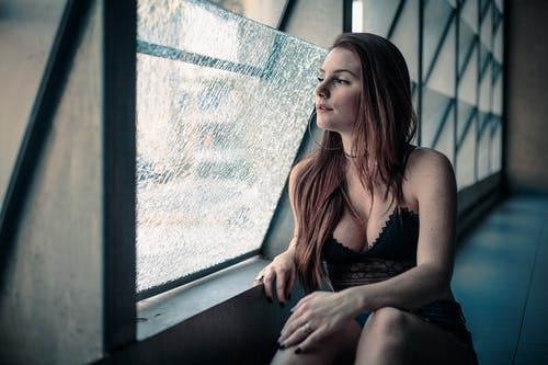 Woman in Black Plunging Neckline Top Looking Through Window