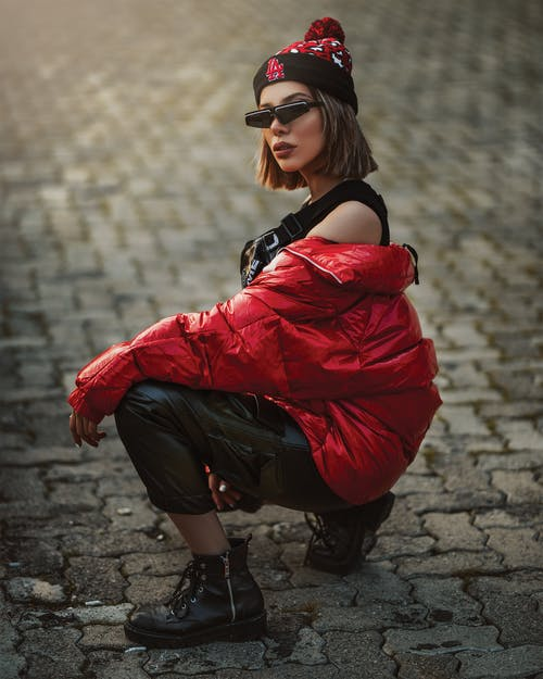 Woman Wearing Red Jacket and Black Sunglasses Sitting on Pavement