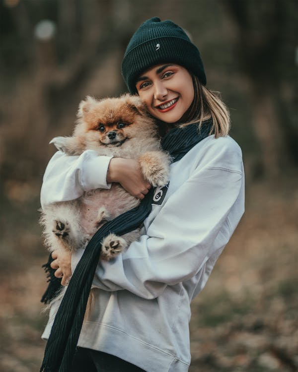 Shallow Focus Photo of Woman Carrying Her Dog