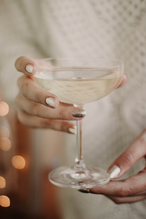 Crop unrecognizable female with shiny nails in white sweater enjoying champagne from elegant glass