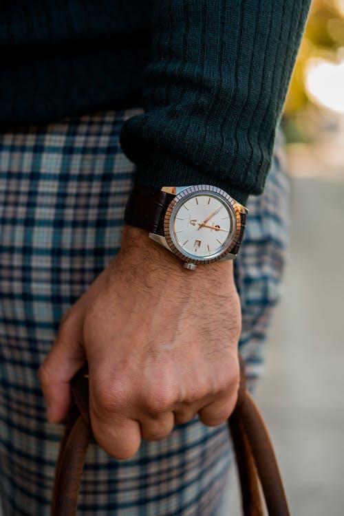 戴黑色和金色模擬手錶的人