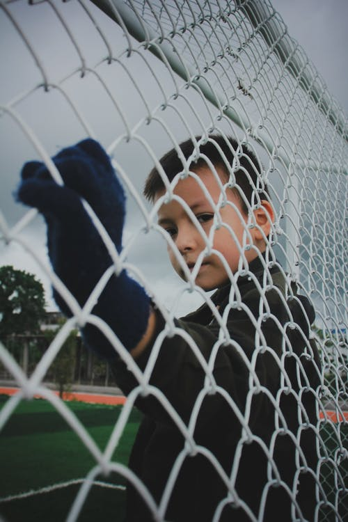 Boy Standing Against Cyclone Fence