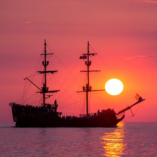 Ship sailing in sea during sunset