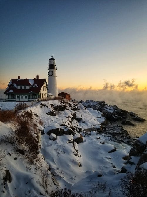 White and Black Lighthouse on Snow Covered Ground