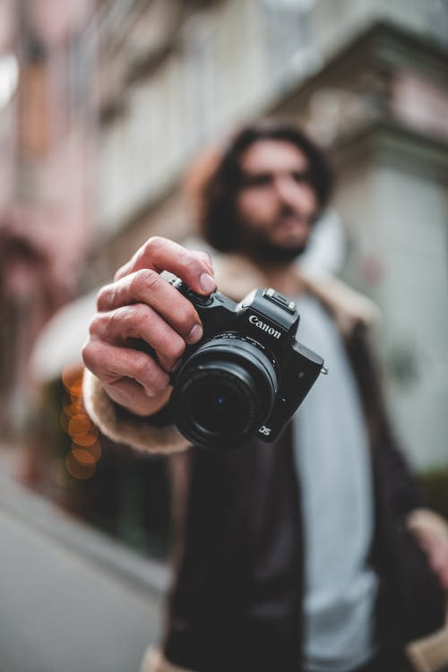 Shallow Photo of Person Holding Black Canon Dslr Camera