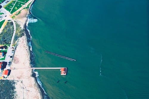 Aerial View of Body of Brown Wooden House Surrounded by Body of Water