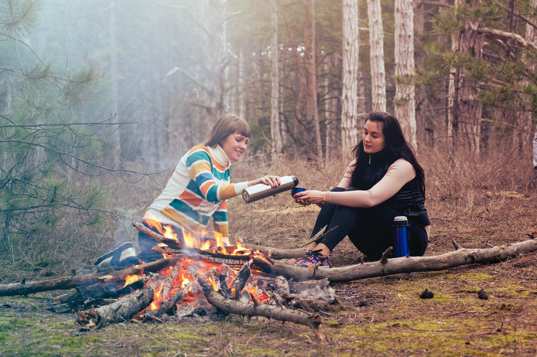 women camping fire two girls