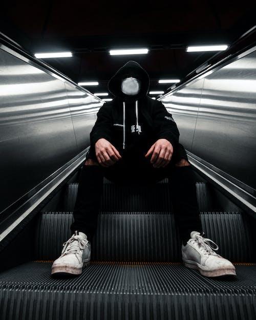 Foto stok gratis alas kaki, celana hitam, duduk, eskalator