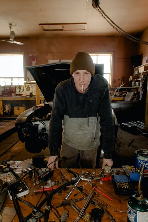 Smoking and Standing Man in Front of Table With Tools