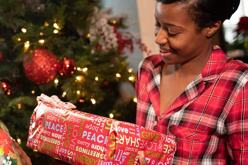 Woman In Red And White Plaid Button Up Shirt Holding A Gift