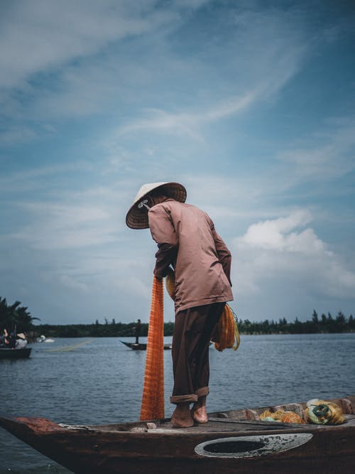 Photo Of Man Standing On Boat