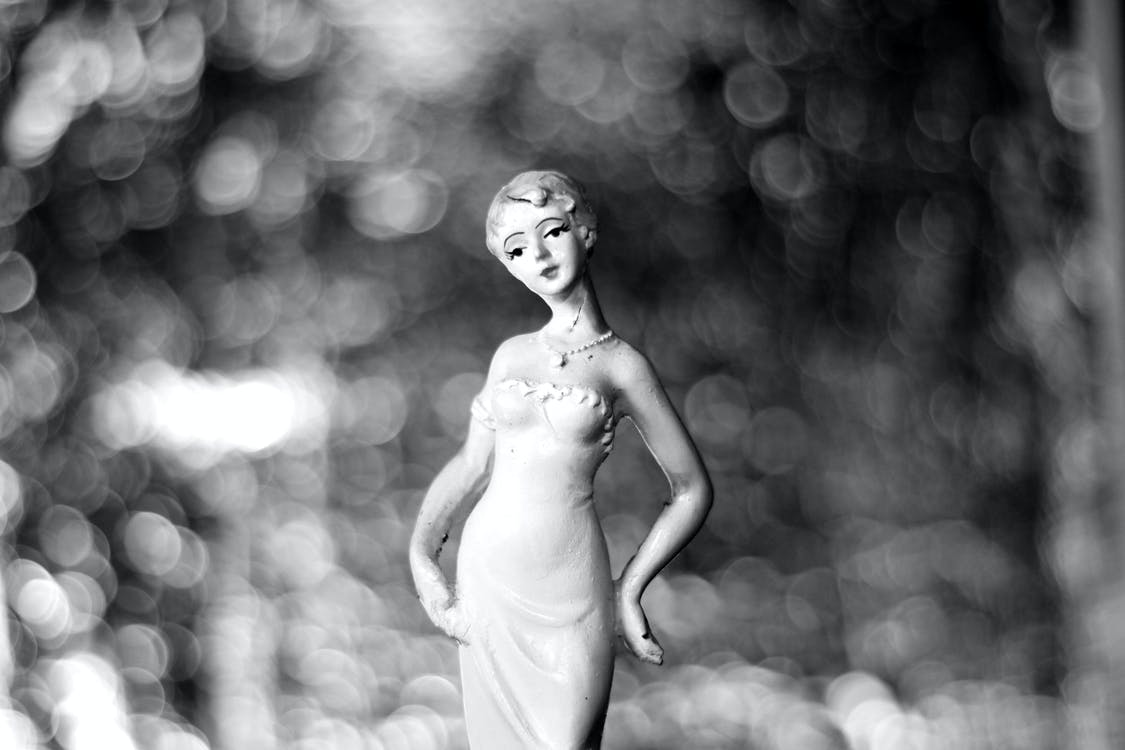 Grayscale Photography of Woman in Dress Figurine