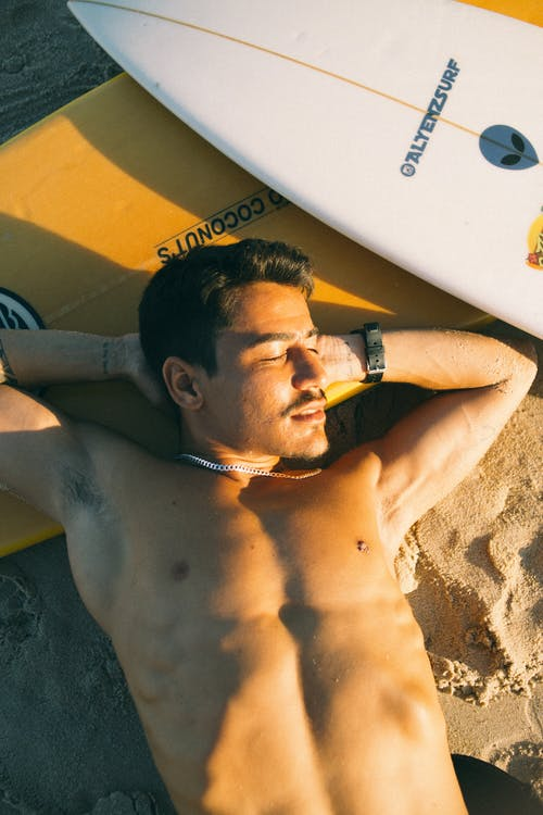 Man Lying On a  Yellow and white Surfboard