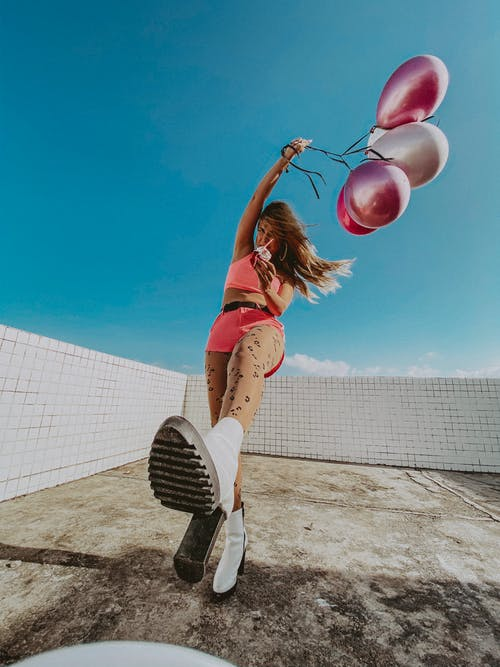 Photo of Woman Posing While Holding Balloons