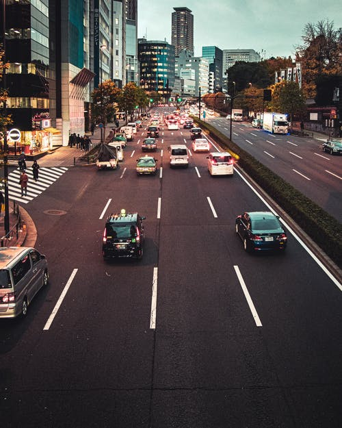 Avenue with cars and vans moving fast past high rise buildings in modern Japanese city in evening