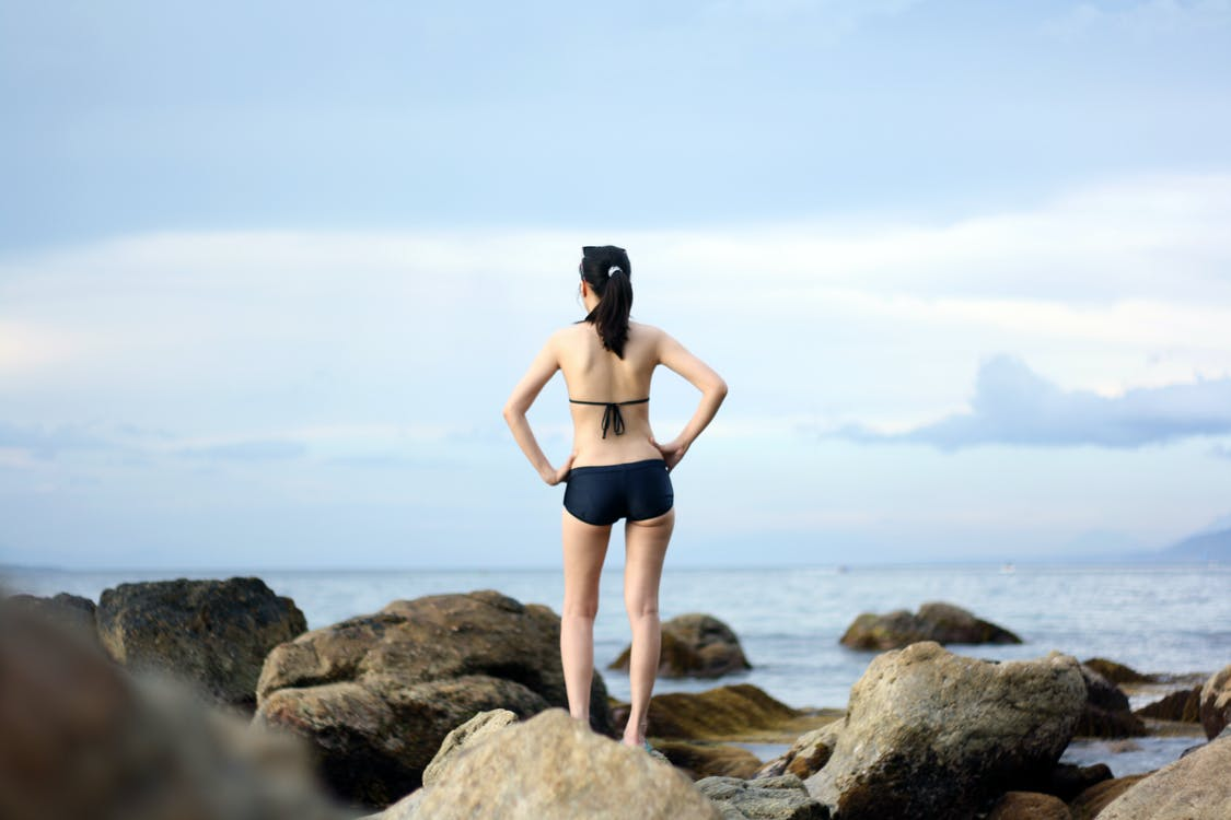 Woman Both Hand Akimbo Standing on Rock Facing Through Body of Water