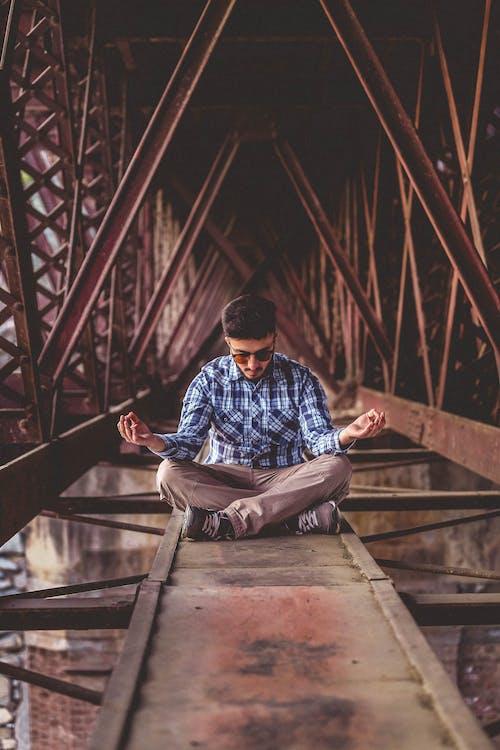 Man Meditating on Metal Surface