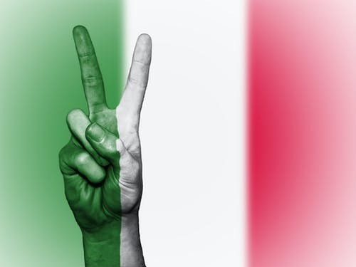 Person's Hand Doing Peace Sign With India Flag Backdrop