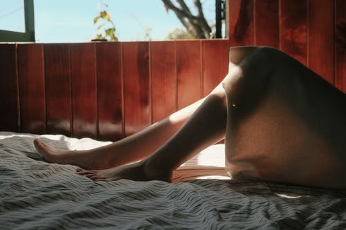 Person Lying on Bed Near Window