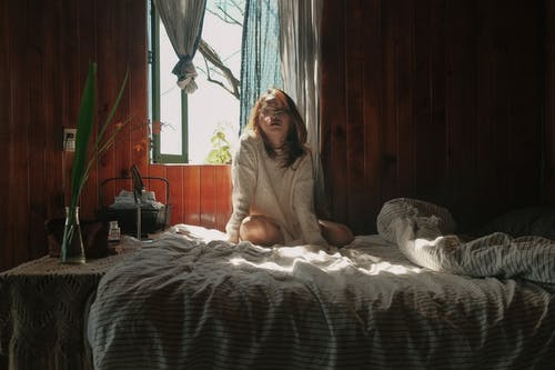 Woman Wearing White Crew-neck Sweater Sitting on Bed Near Open Window
