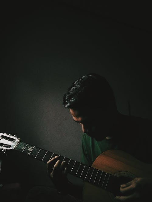 Musician playing acoustic guitar in darkness