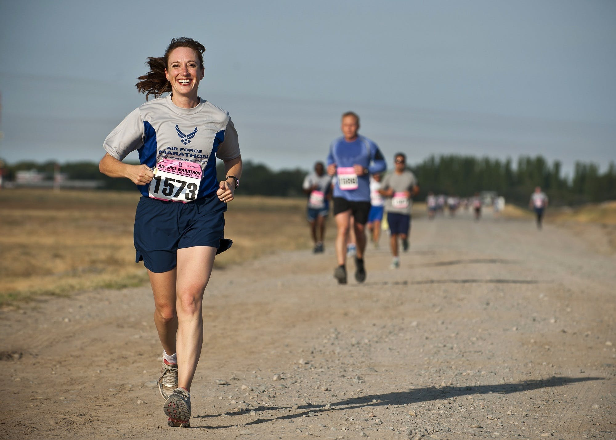 Woman in Gray Crew Neck Shirt Running on Brown Soil during Daytime