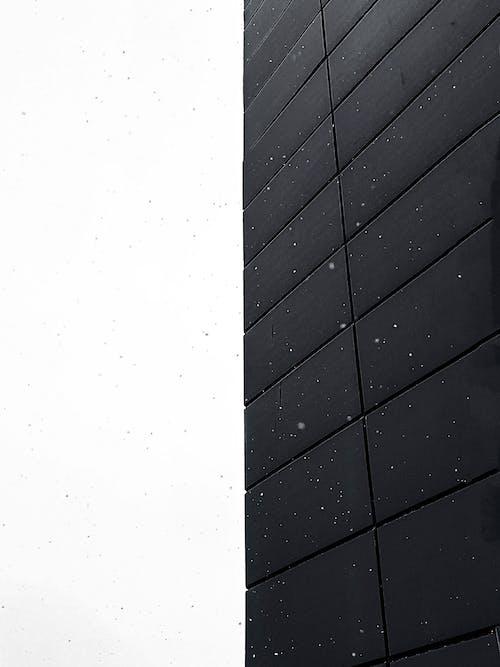 Tiled black wall of modern building against white sky