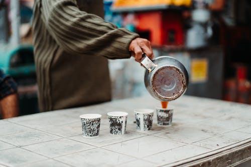 Persona Che Versa Il Caffè Su Una Tazza