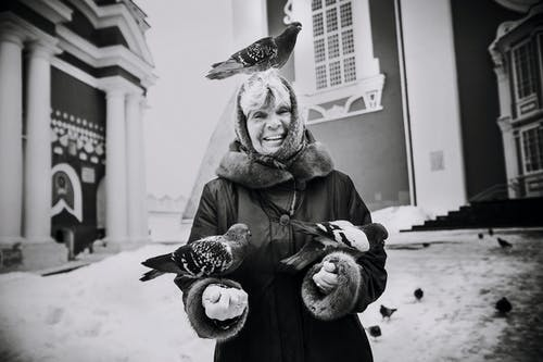 Monochrome Photo of Woman With Perched Pigeons on Her