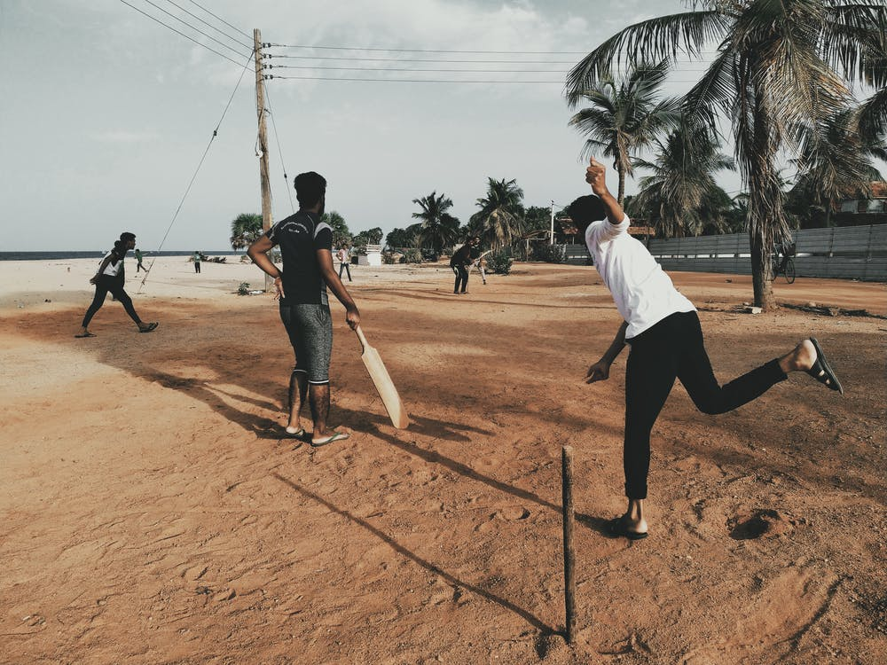 Men Playing Cricket at Beach