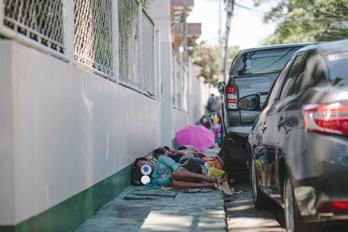 People Lying on Pavement Beside Parked Vehicles
