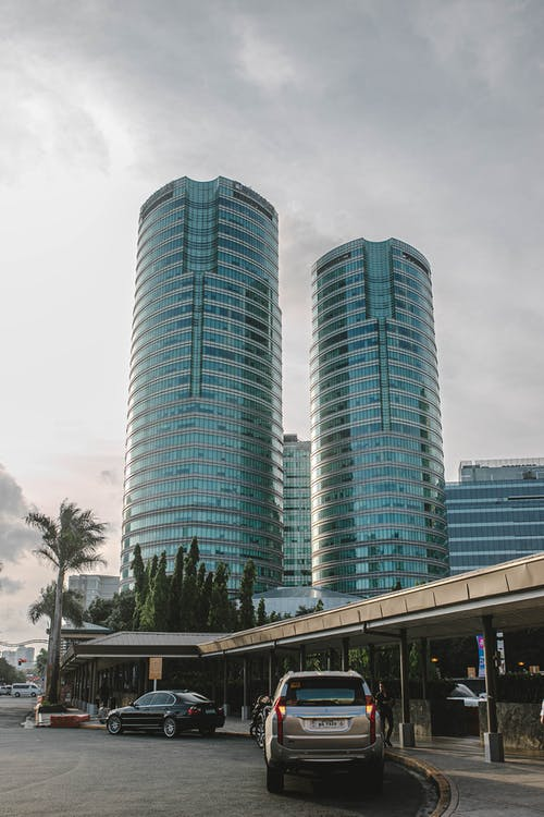 Few Vehicles Parking Near Road Viewing High-rise Buildings Under Gray Sky