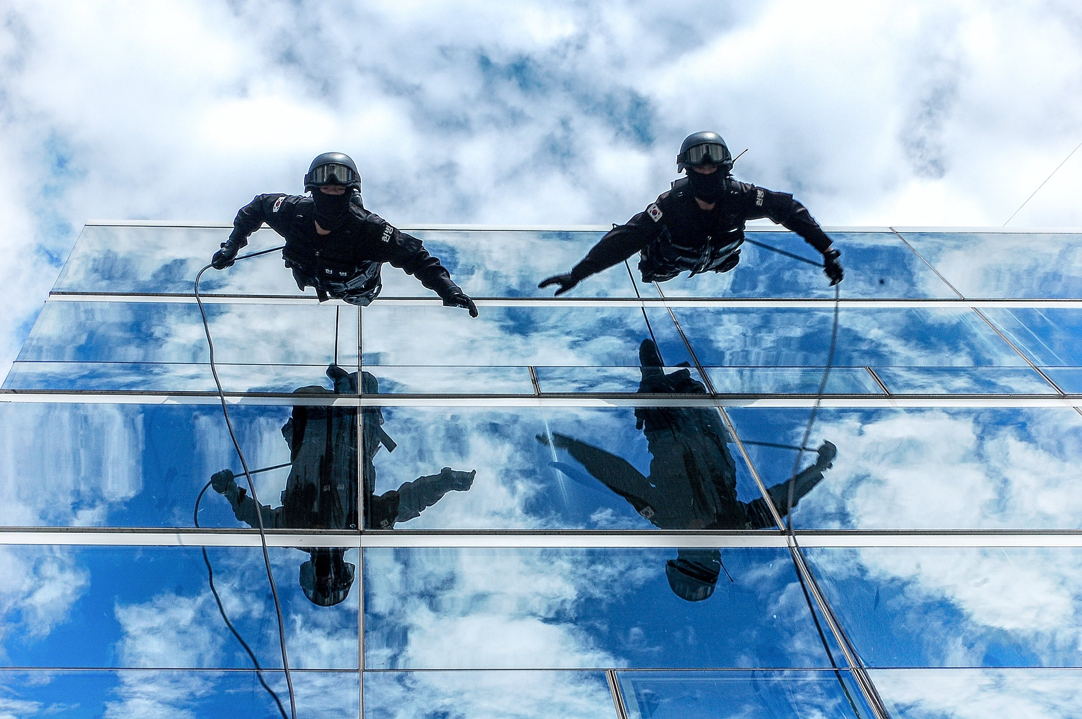 Two People on Building Glass Wall Under Cloudy Sky