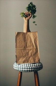 Right Human Hand Holding Green Vegetable on Paper Bag