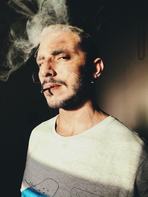 남자 흡연과 회색 셔츠를 입고